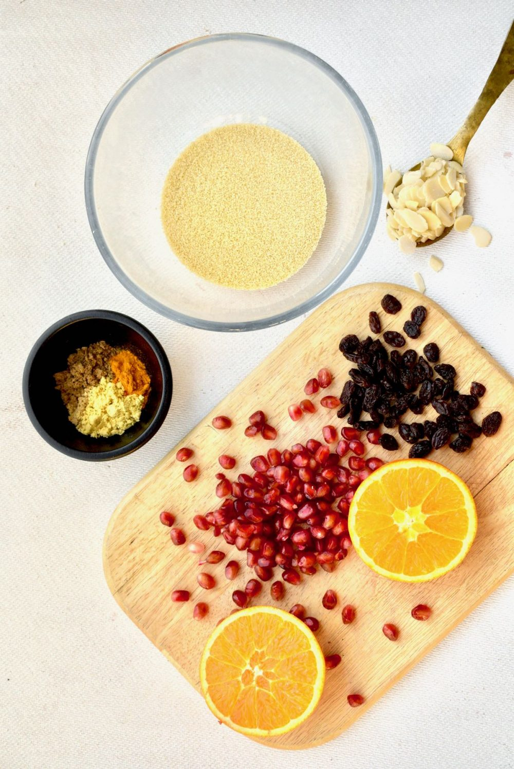 A pot of spices, a bowl of couscous, flaked almonds and fruits laid out on a board