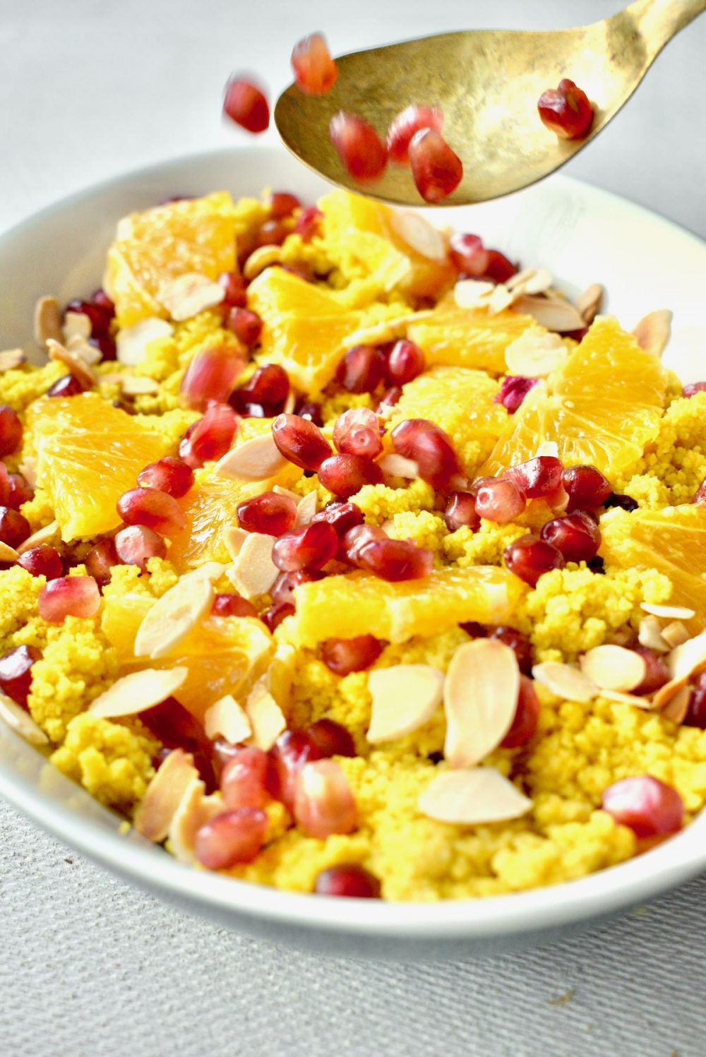 The pomegranate seeds are caught in mid air as they fall from a spoon on to the couscous