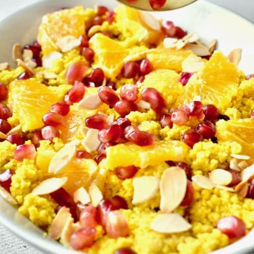 Bright yellow couscous topped with oranges, almonds and pomegranite arils in a white dish
