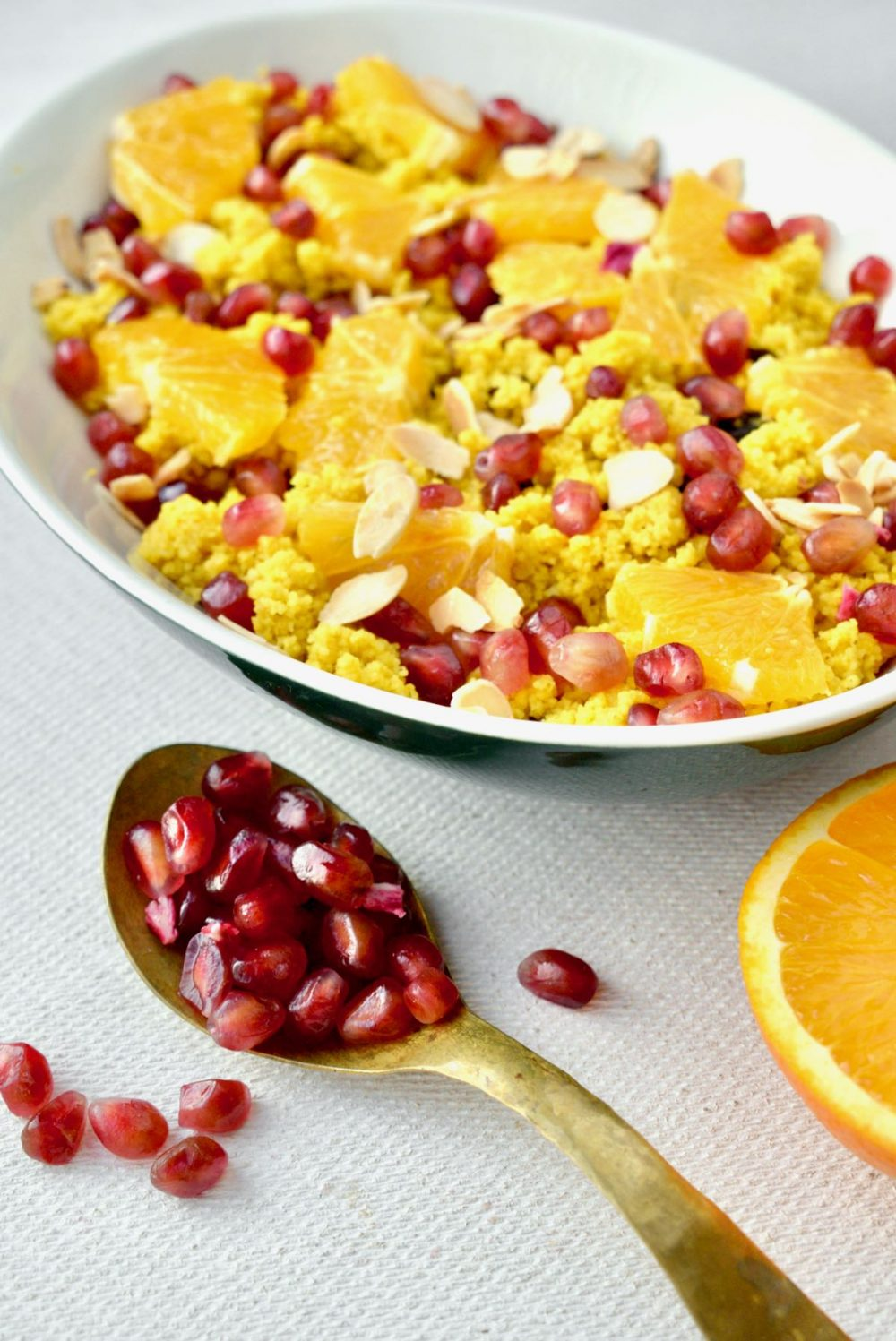 Bright sunshine coloured couscous covered in orange pieces, red pomegranate arils and toasted nuts