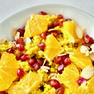 Sunshine yellow couscous topped with oranges, pomegranite and nuts