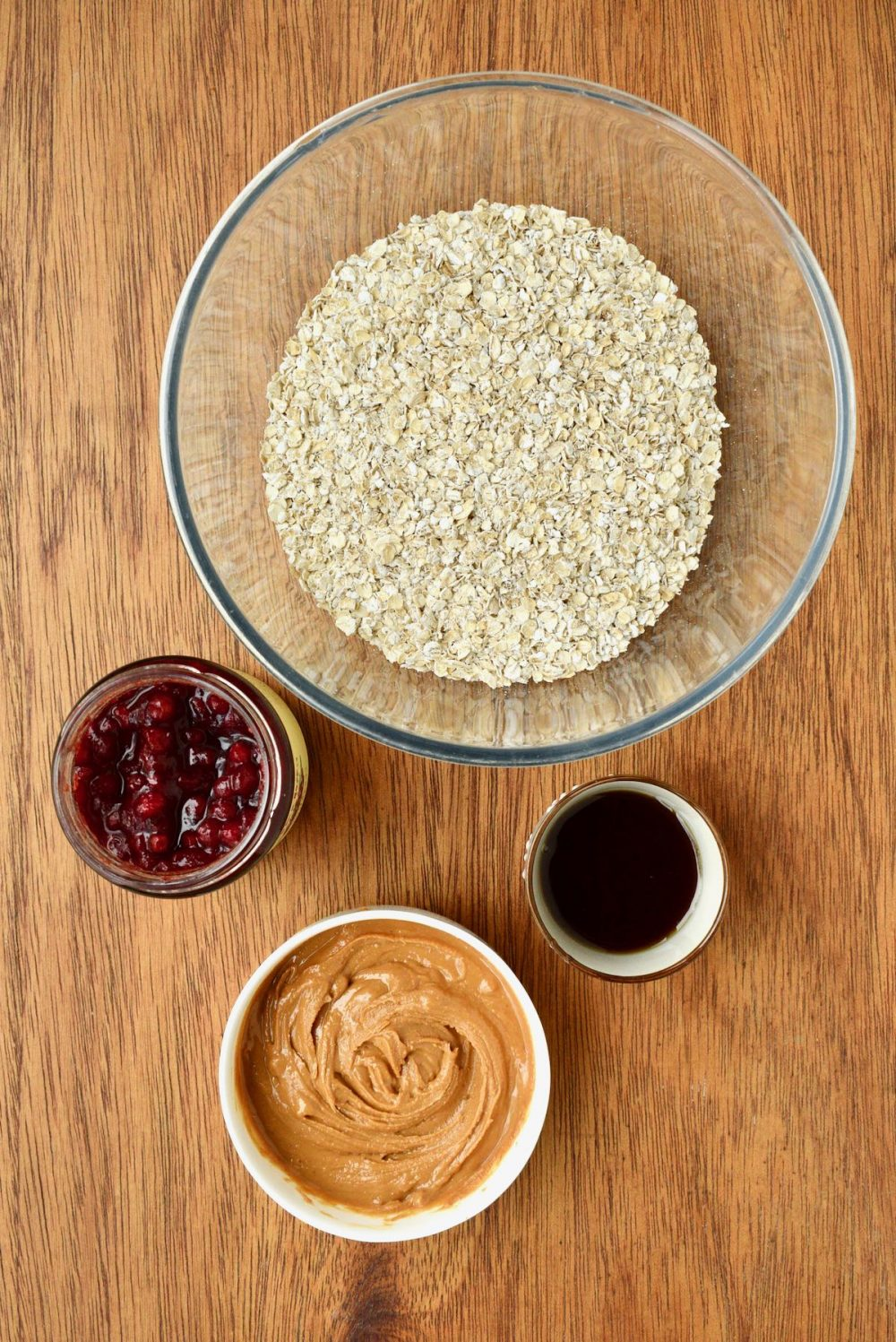 Ingredients on a wooden board - a bowl of oats, jar of jam, maple syrup and smooth peanut butter