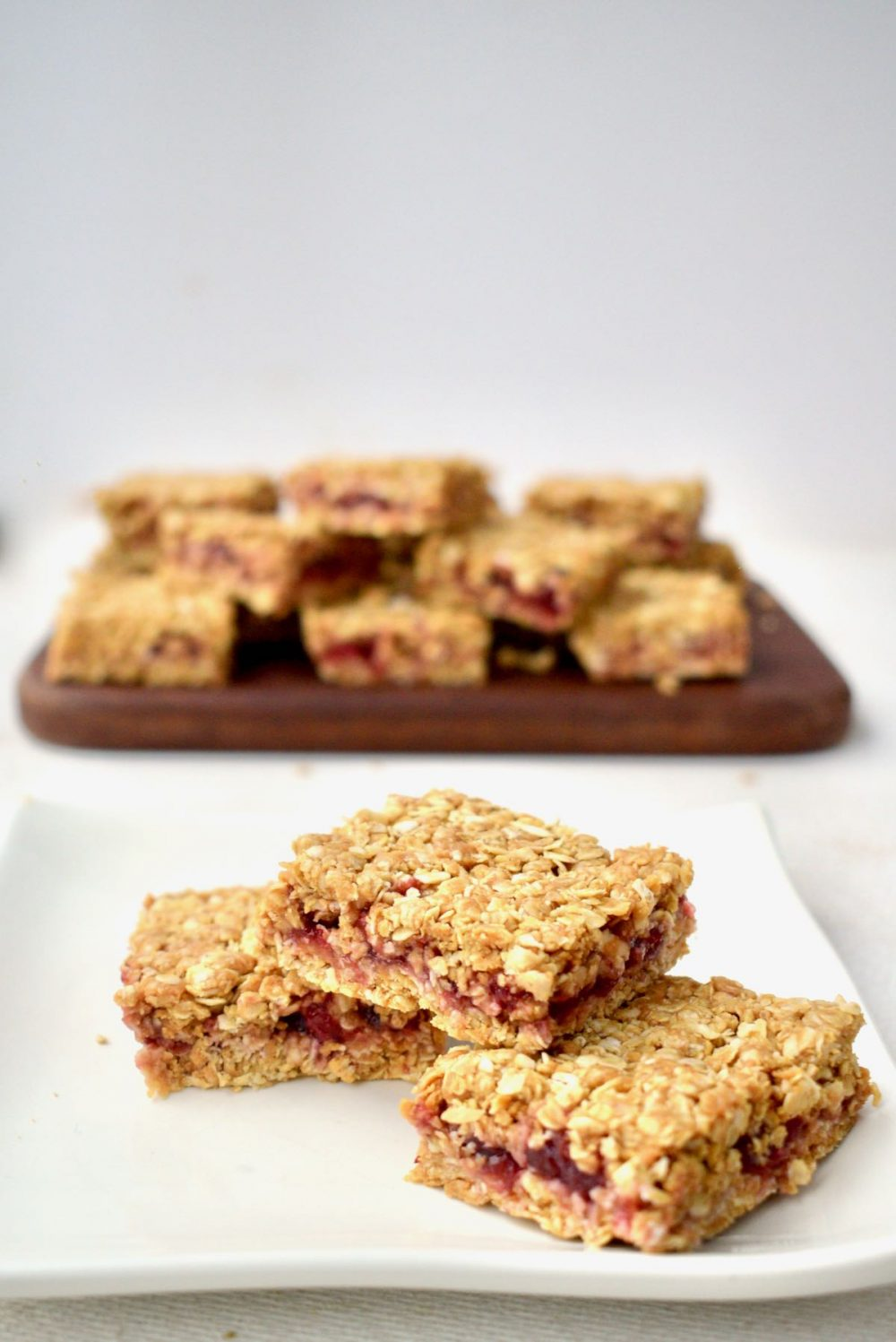 Three vegan oat bars on a plate, with the remaining bars in the background