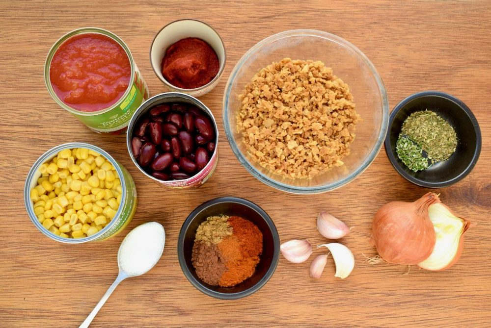 The ingredients laid out on a wooden board - canned tomatoes, beans and corn, spices, herbs, dried soy mince, onion and garlic.
