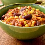 Cooked beans, sweetcorn, fried herbs and a tomato and soy mince sauce in a bowl