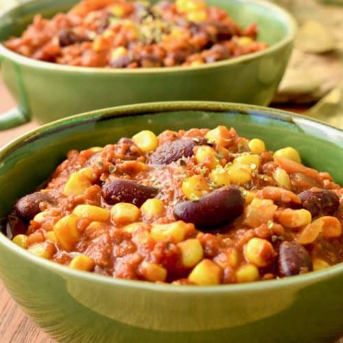 Two green bowls of colourful vegan chilli made with beans, sweetcorn and tomatoes