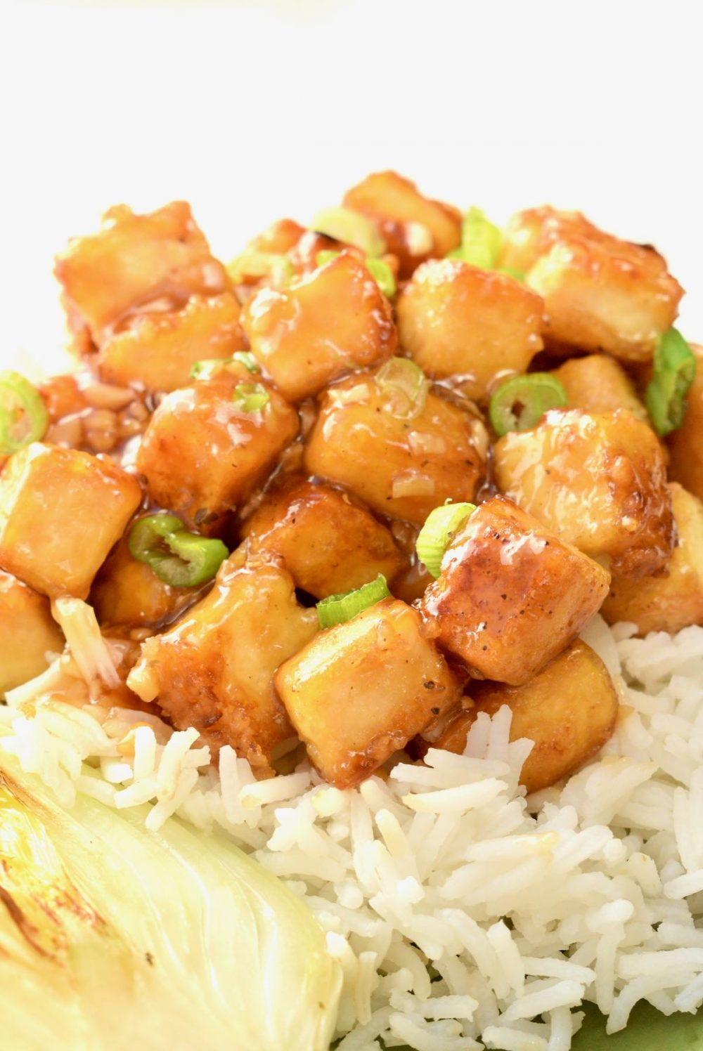 A sticky, shiny lemony sauce covering cubes of tofu on top of white rice
