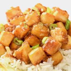 Cubes of tofu on white rice covered in a lemon sauce and garnished with spring onion