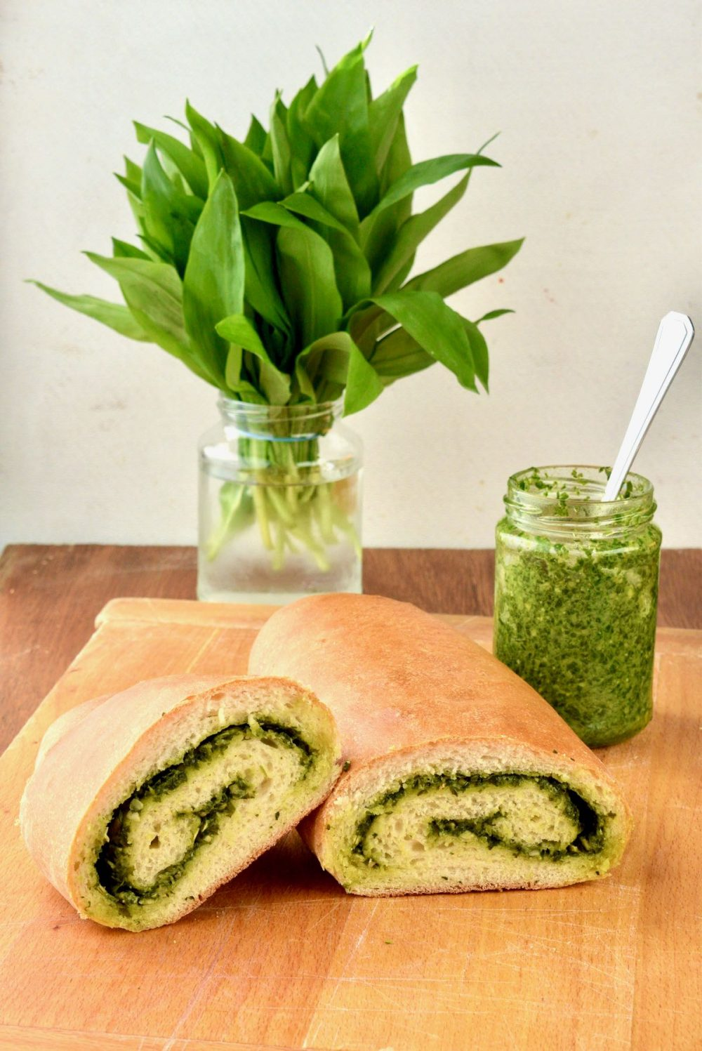 The baked loaf has a golden crust and is cut open to reveal the green swirl of pesto inside