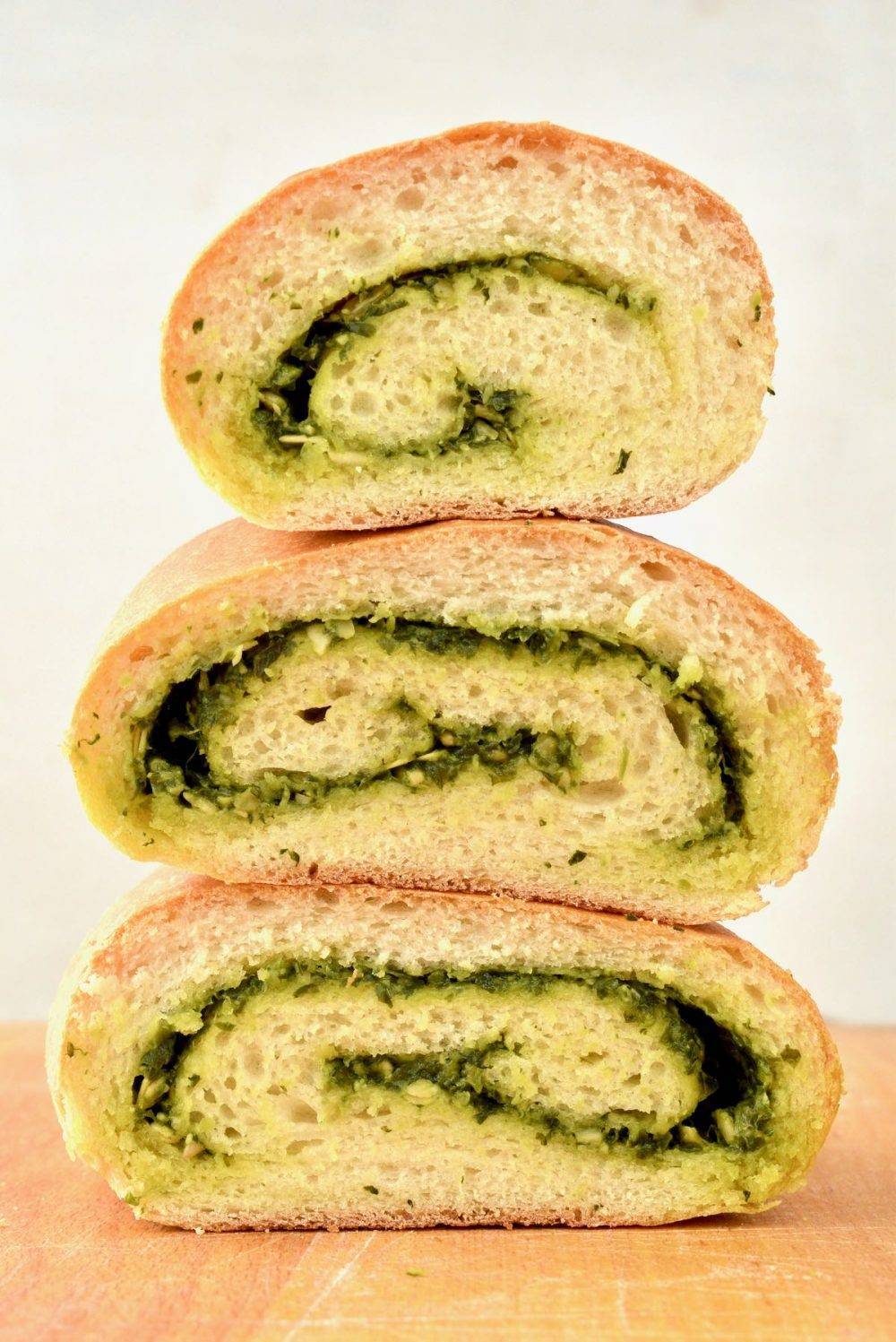 Three slices of pesto swirl bread stacked on top of each other