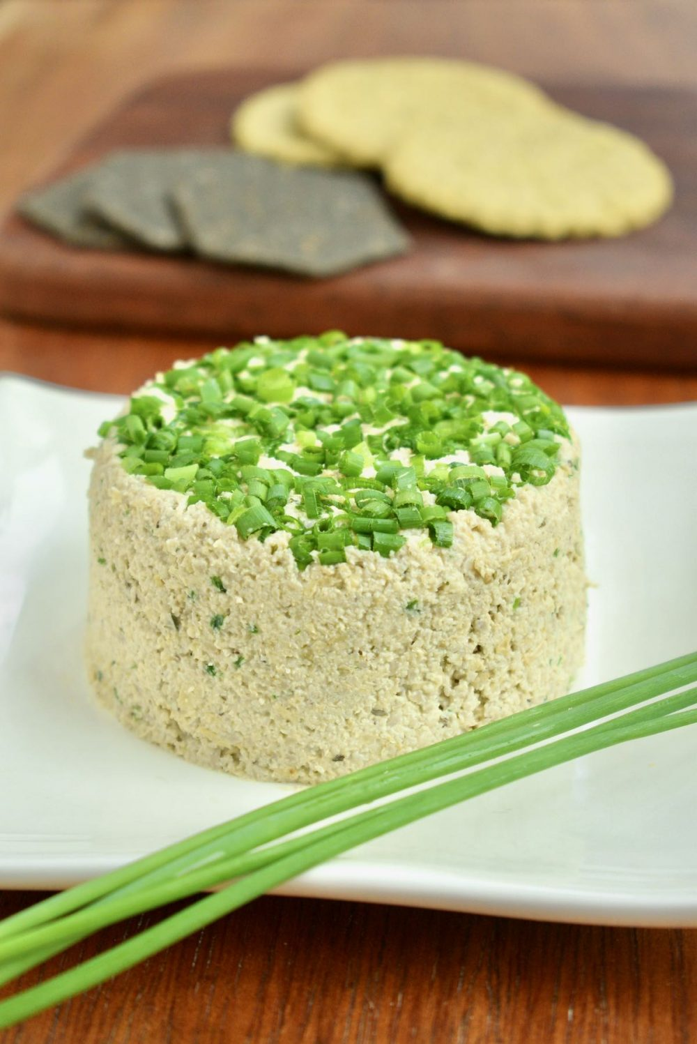 The finished 'cheese' is topped with chives and sits neatly on a white plate.