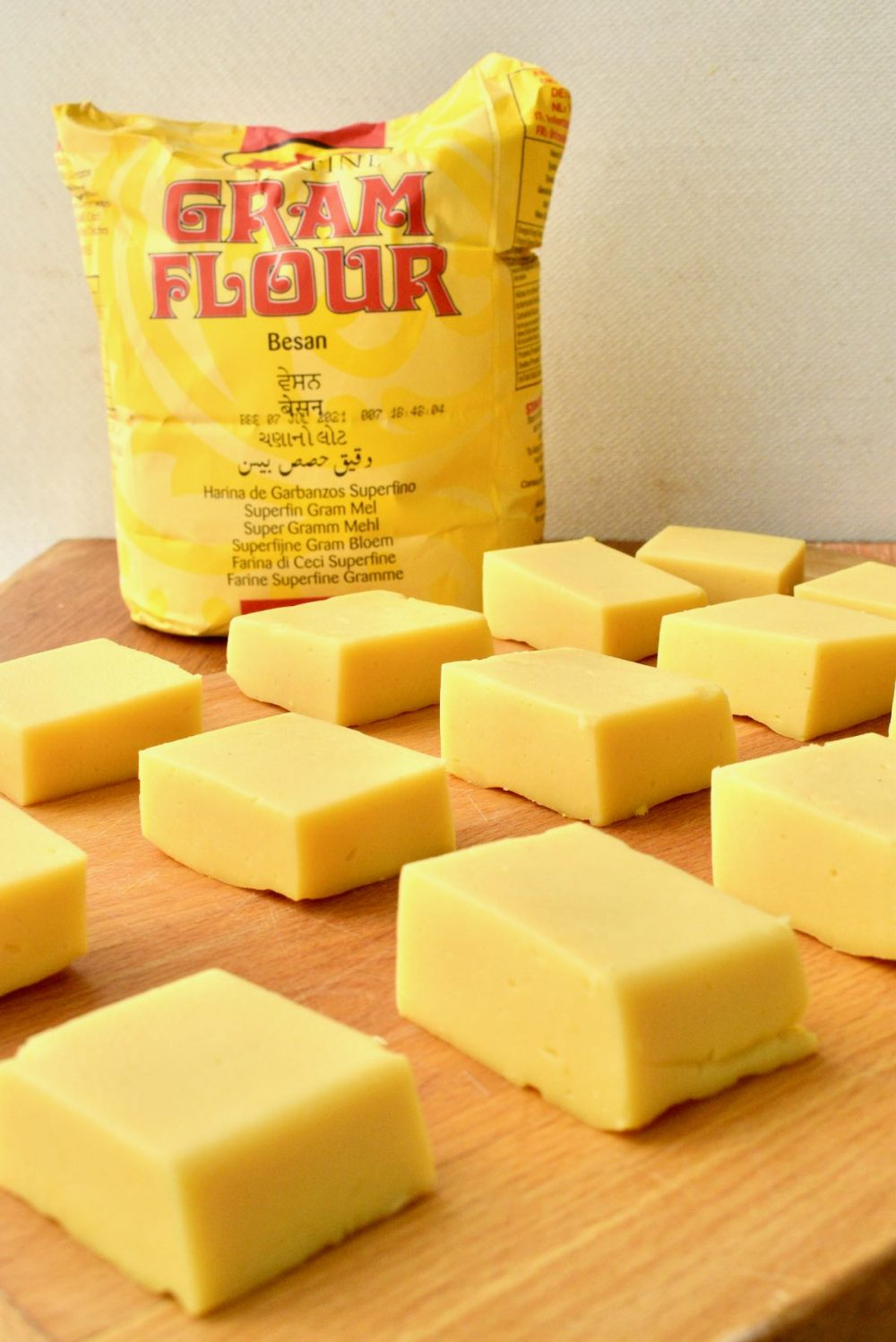 Slices of yellow tofu on a wooden board in front of a bag of gram flour
