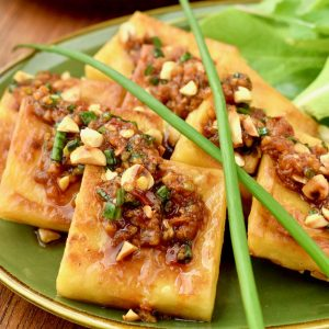 Squares of yellow chickbea tofu drizzed in a sauce and garnished with peanuts and chives