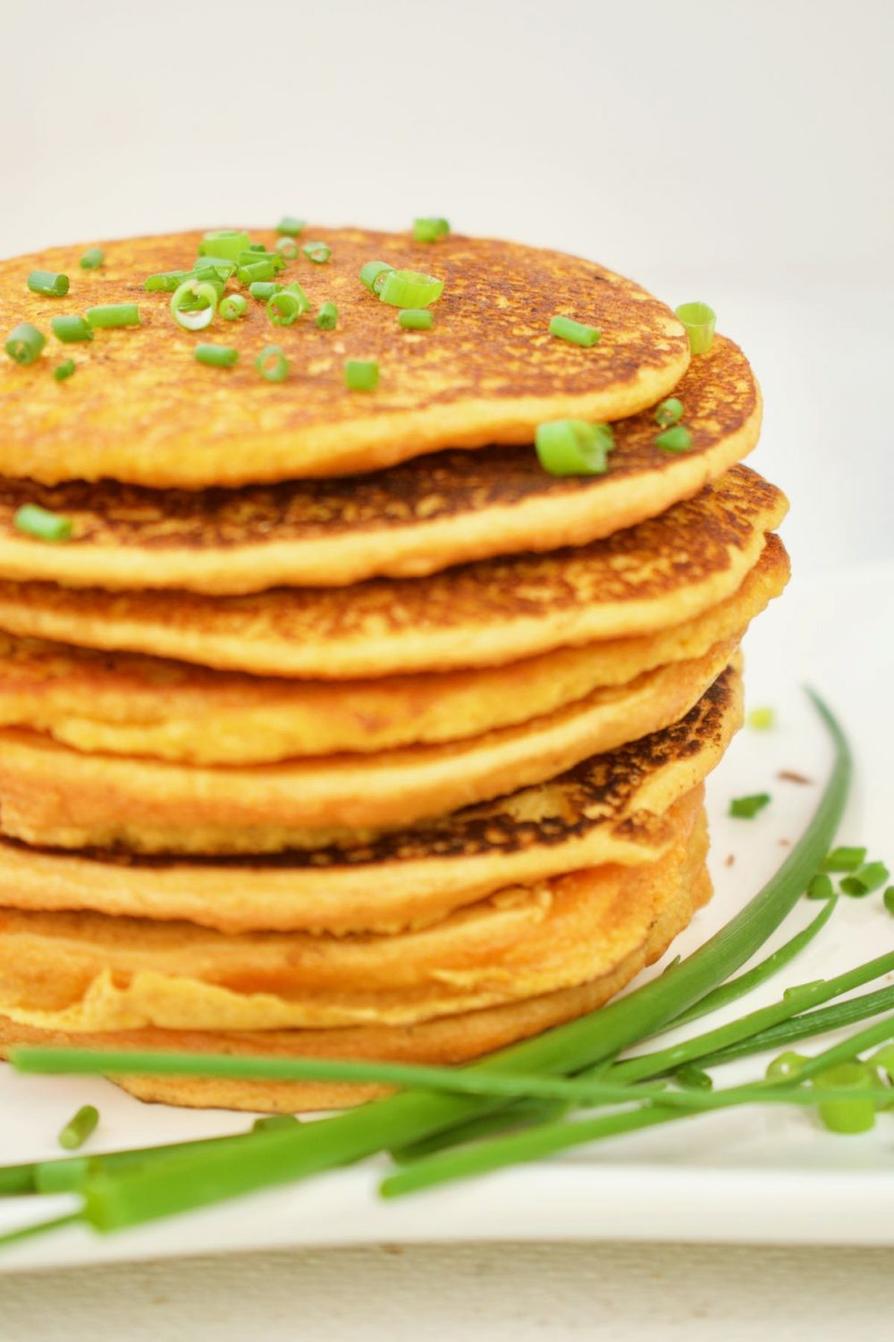 The finished red lentil flatbreads are stacked up on a plate, with bright green chives as a garnish.