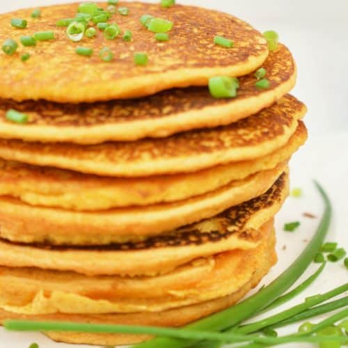 A stack of orange coloured, round flatbreads, garnished with green chives