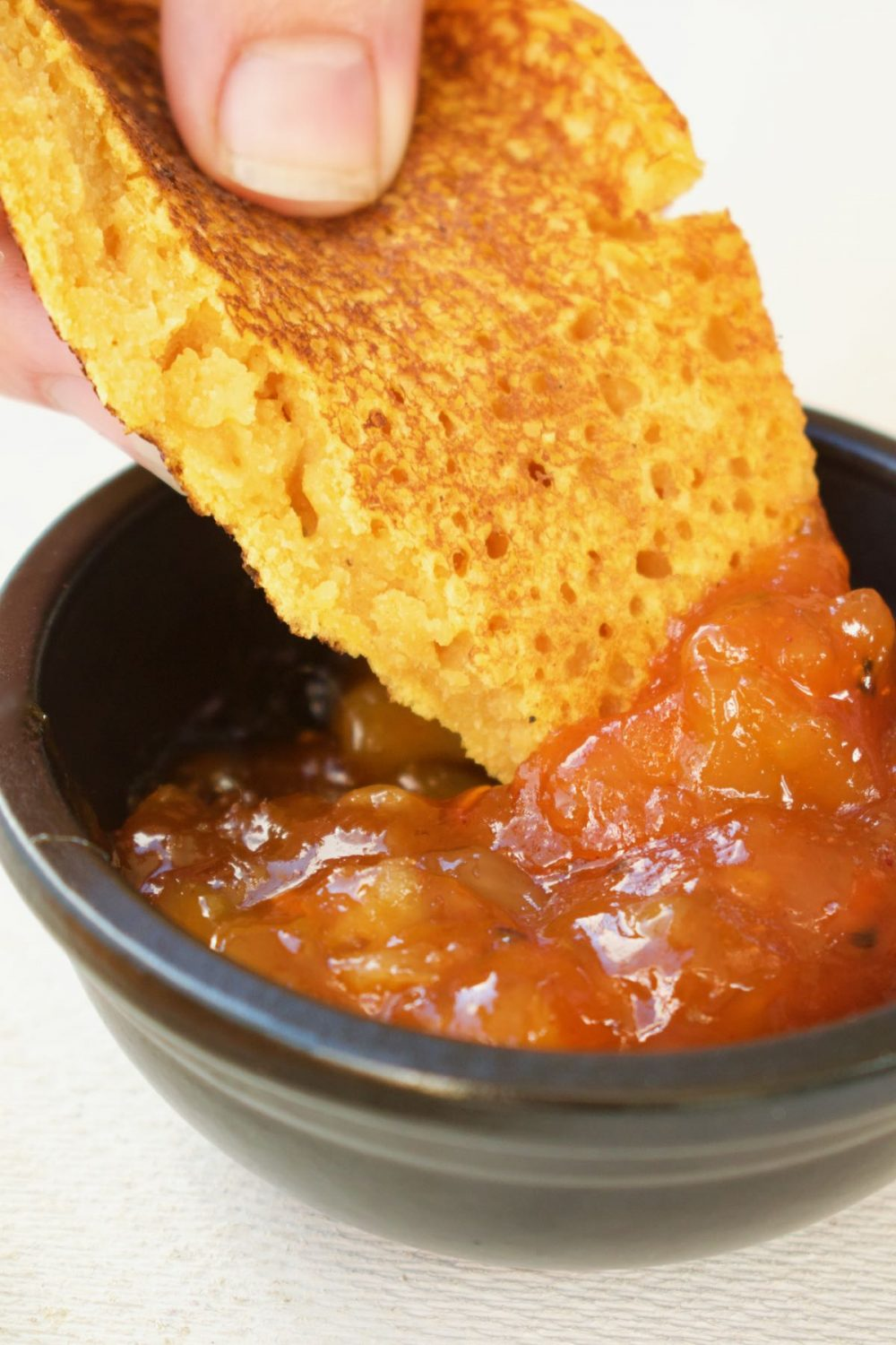 Dipping the flatbread in a black pot of mango chutney