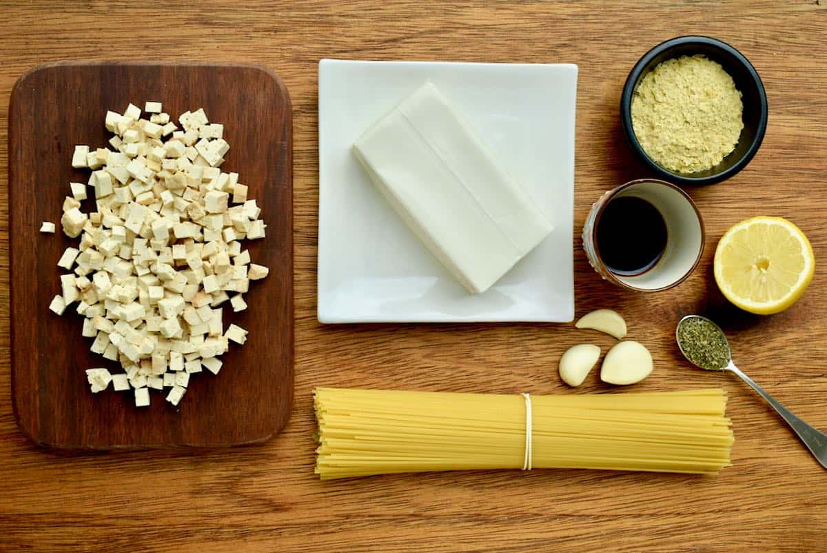 All the ingredients laid out on a wooden board - cubes of smoked tofu, a bunch of spaghetti, a block of silken tofu, garlic, herbs, soy sauce, lemon and nutritional yeast.