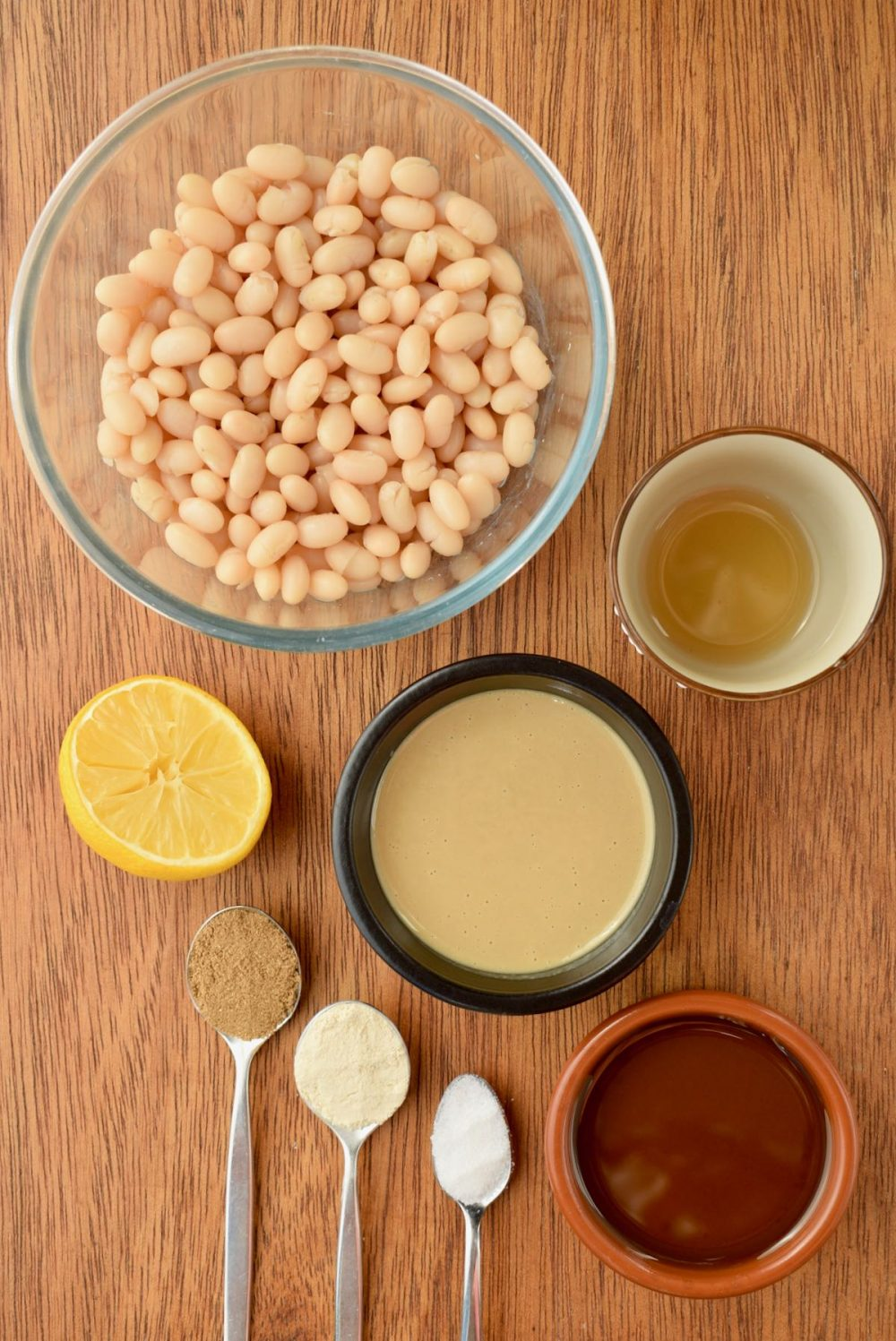 Ingredients laid out on a wooden board - a bowl of beans, half a lemon, tahini, vinegar, olive oil and spoonfuls of coriander, garlic powder and salt.