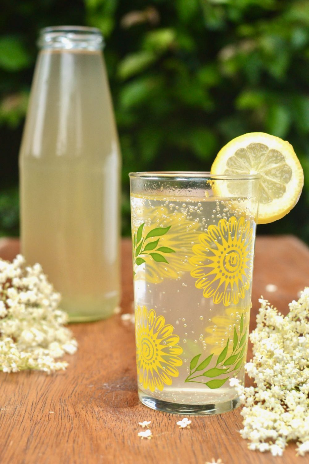 A glass of elderflower cordial mixed with water, and a bottle of homemade cordial behind