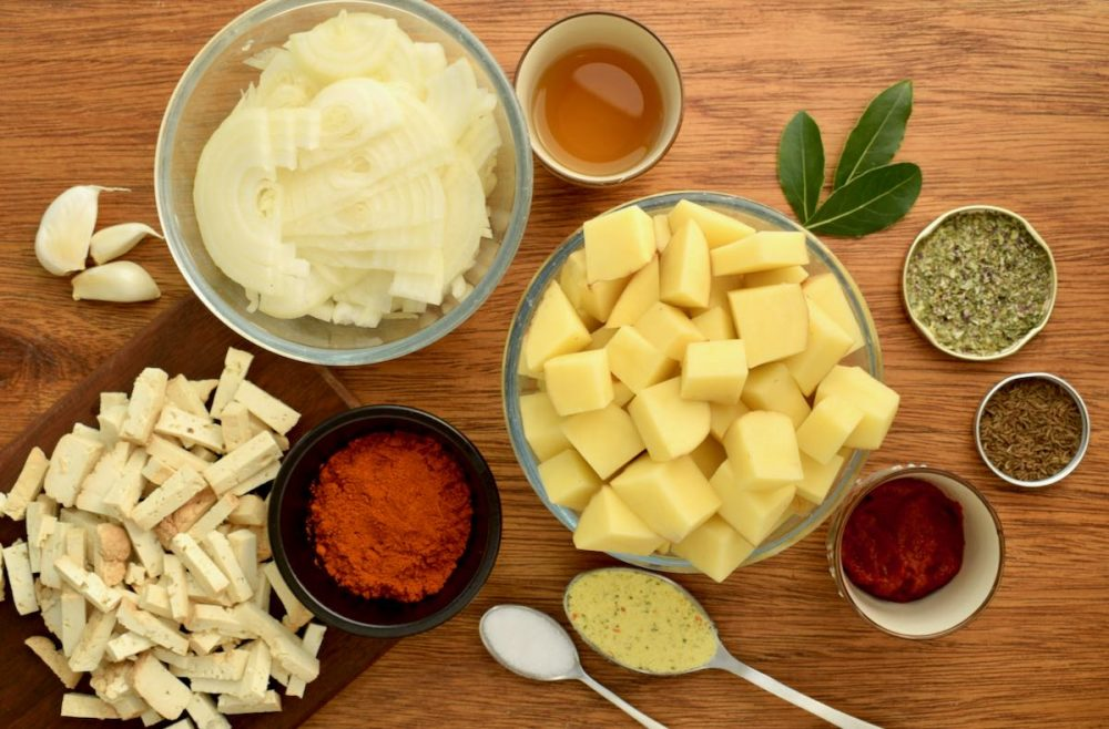 The ingredients for vegan goulash on a wooden board - diced potatoes, tofu and onion, alongside spices and seasonings