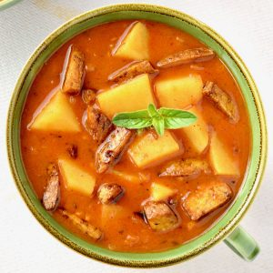 A bowl of red potato goulash. Potatoes are sitting on the surface, and the bowl is topped with bits of fried tofu and a leaf of marjoram.