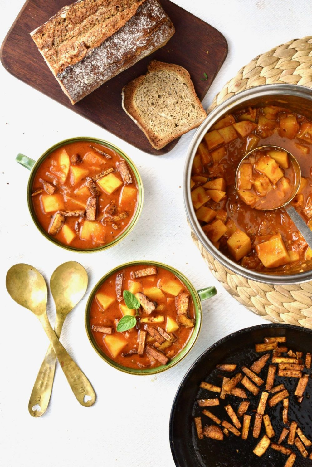 A pan of goulash with a ladle, a frying pan with cubes of tofu, a board with bread on and two bowls of goulash.