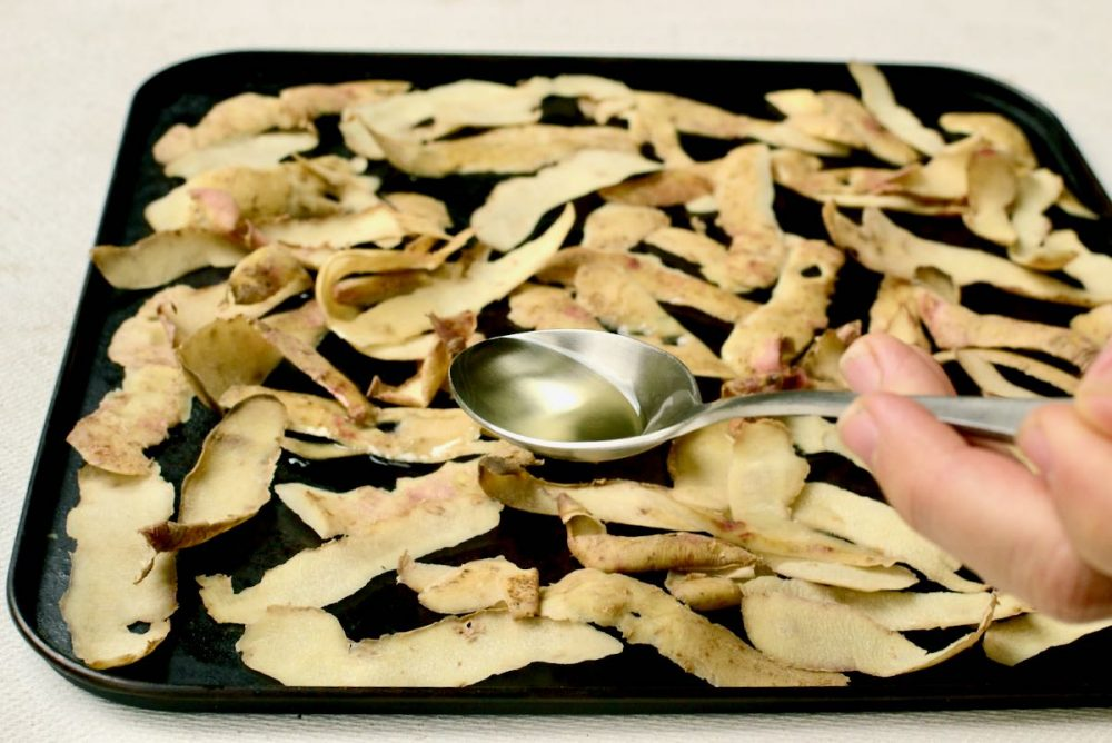 A spoon drizzles oil over potato peels on a baking sheet