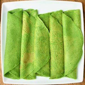 Five bright green rolled up spinach pancakes sitting next to each other on a square white plate