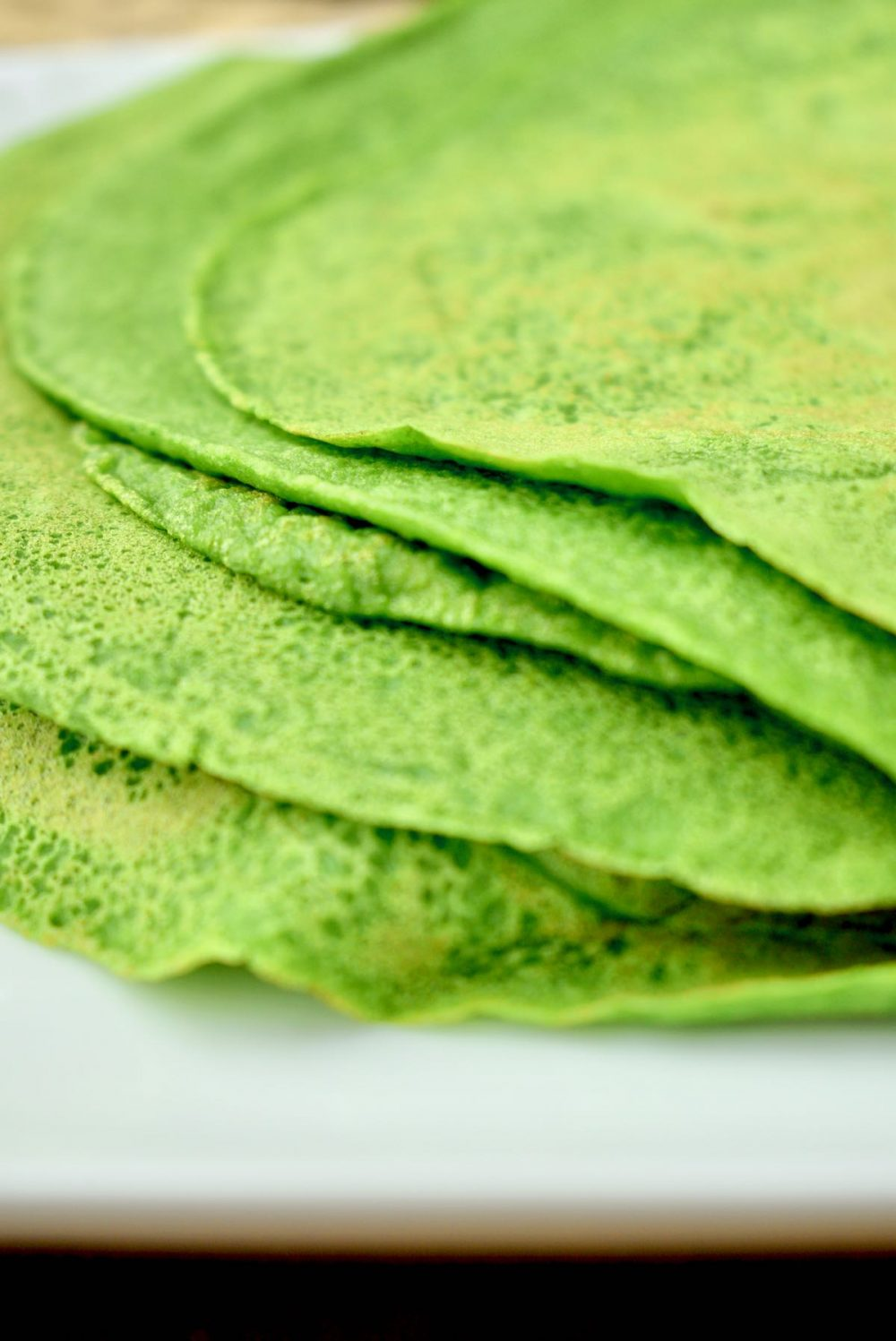Five bright green, thin, crepe style pancakes on a white plate