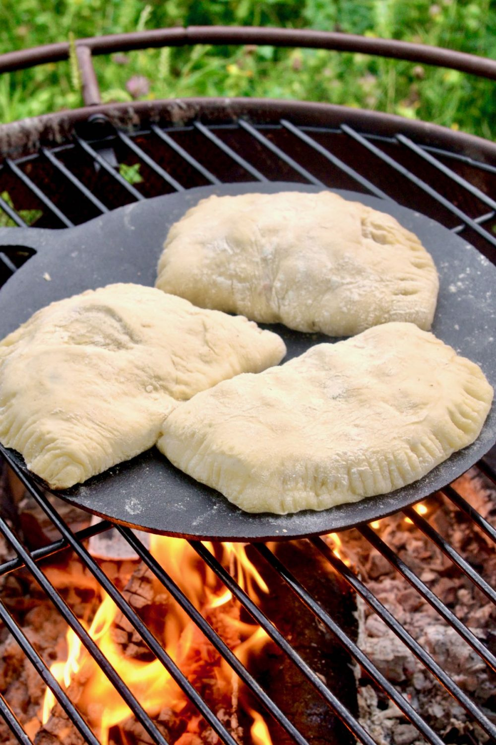 Three calzone are cooking on a cast iron baking stone set on a grill above a firepit.