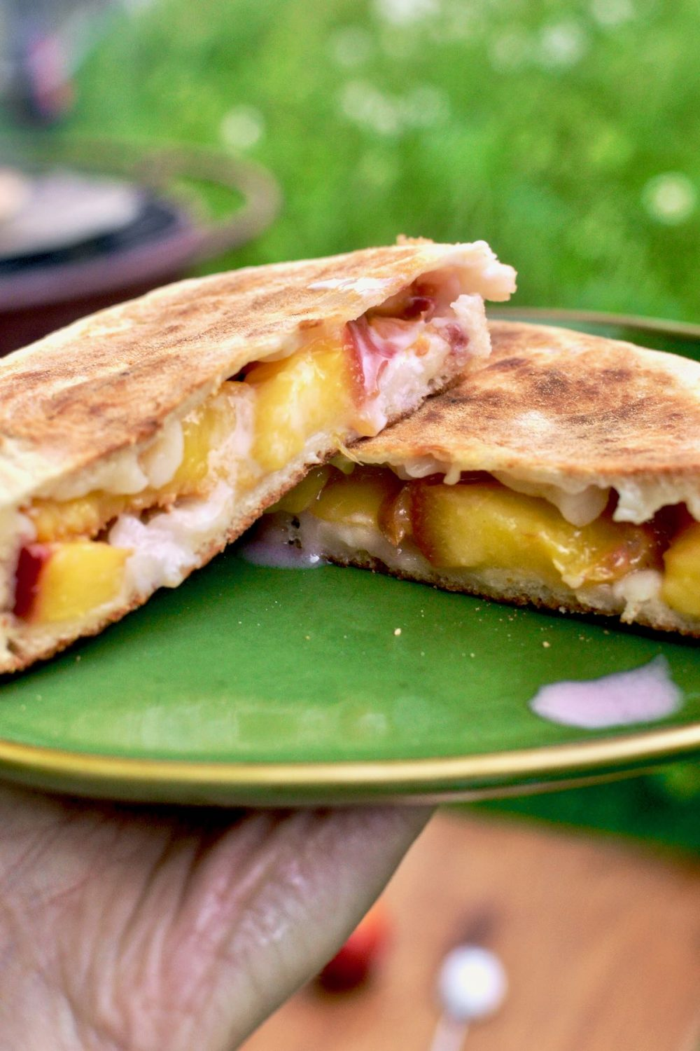 A calzone is cut in half, revealing the filling of fresh peach slices and coconut cream.