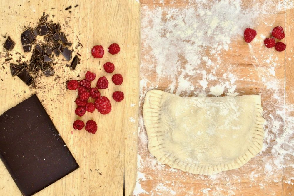 A bar of chocolate and some raspberries on a wooden board. Next to it, an already filled calzone.