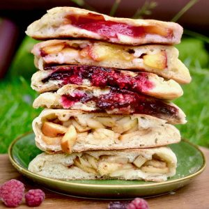 Different filled sweet pizzas cut in half and stacked on top of each other: There are fillings of peach and coconut cream, raspberry and chocolate, and apple and cinnamon.