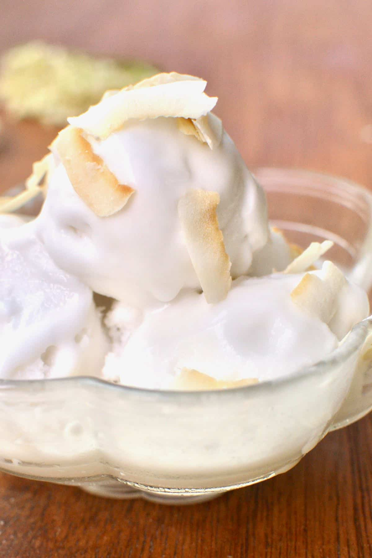 A bowl of three scoops of white elderflower coconut ice cream, topped with chips of dessiccated coconut