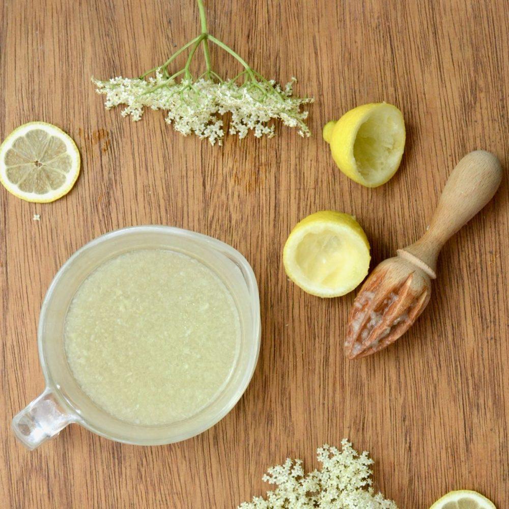 A jug with lemon juice, next to a lemon squeezer