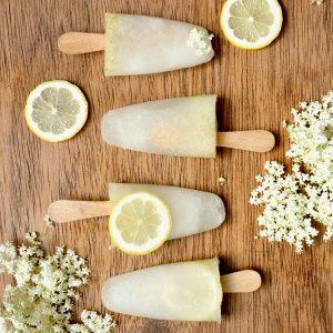 Frozen elderflower ice lollies arranged in a row on a wooden board