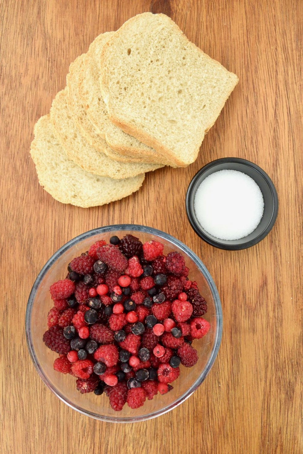 The ingredients for the summer pudding laid out on the table: slices of white bread, a small bowl of sugar and a big glass bowl filled with a variation of red berries.