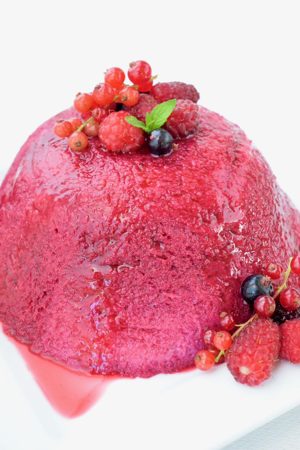A juicy dome shaped finished pudding sitting on a white plate and decorated with fresh red fuit.