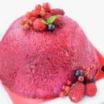 A deep red and juicy dome shaped pudding sitting on a white plate and decorated with fresh red fuit.