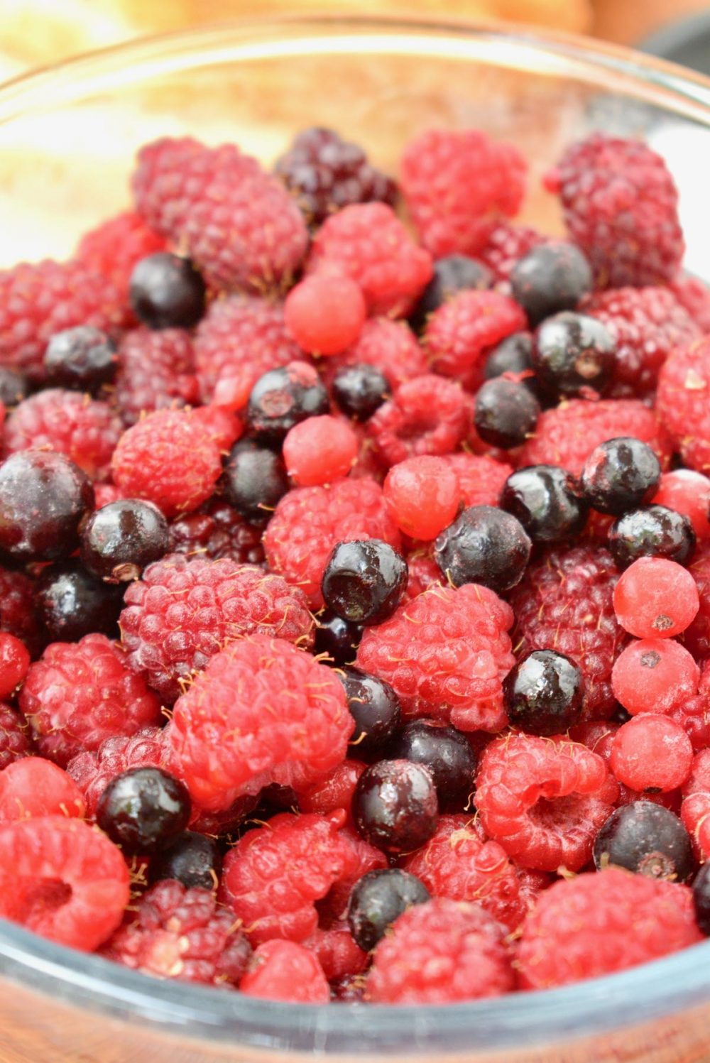A glass bowl filled to the rim with mixed red berries: raspberries, strawberries, blackberries, blueberries and both red and black currants.