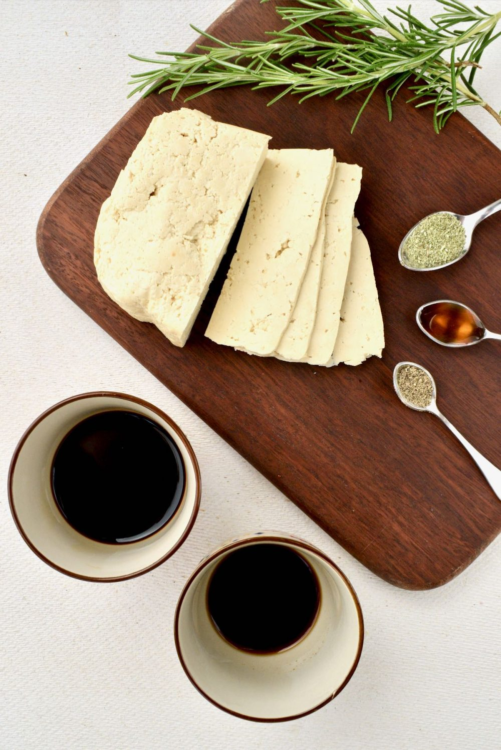 An arrangement of the recipe's main ingredients: tofu slices on a dark wooden board, ground rosemary, maple syrup and black pepper on small measuring spoons, and soy sauce and liquid smoke in small pots.