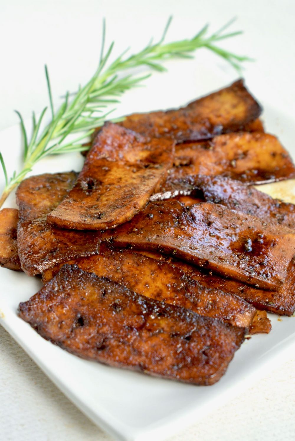 A juicy pile of dark brown, fried slices of tofu on a white square plate, decorated with a twig of fresh rosemary.