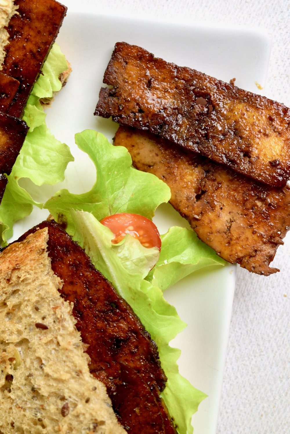 A top down view of a bacon tomato and lettuce sandwich next to some slices of the fried tofu that has been prepared to imitate the texture and flavour of bacon.