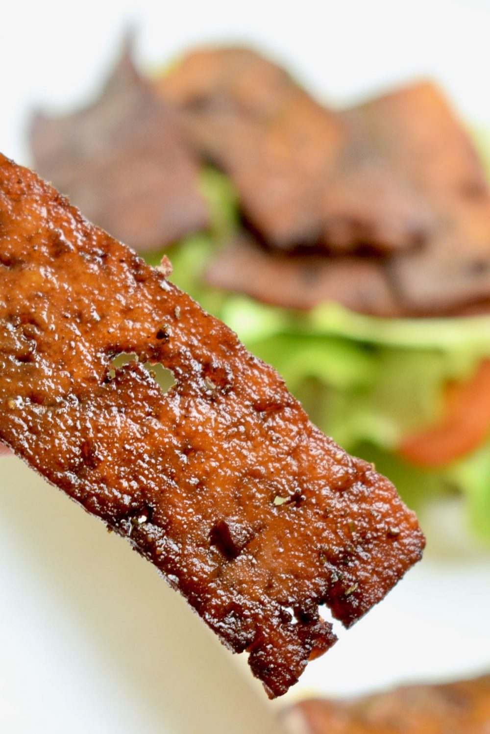 A slice of fried tofu shows off its texure close-up. It is shiny with oil and juicy with marinade, crisp and dark in some spots and thin and porous in others.