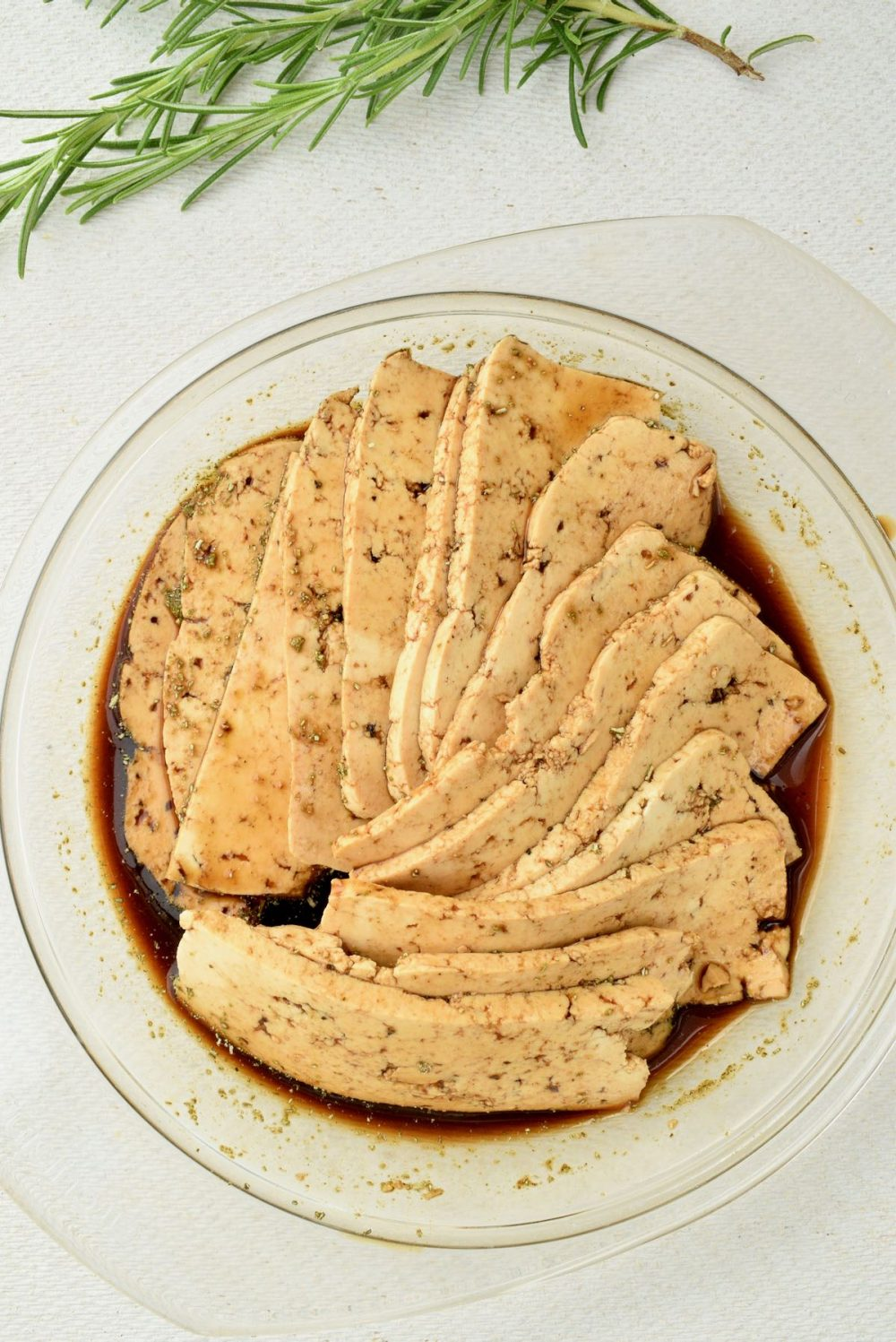 In a shallow glass dish, the tofu slices are fanned out and marinating in the dark brown liquid.