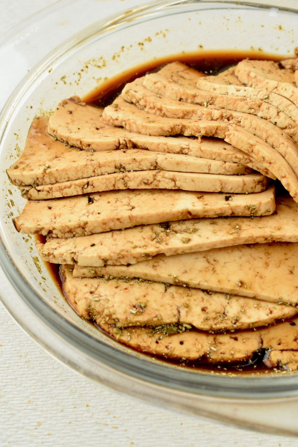 In a shallow glass dish, the tofu slices are marinated in the dark brown marinade.