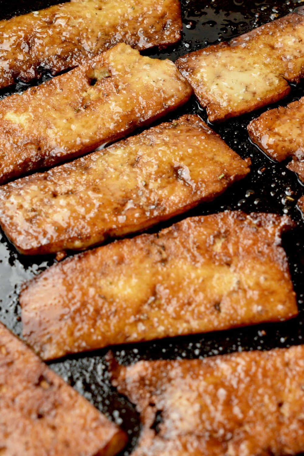 A close up of some slices of marinated tofu being fried golden brown in a frying pan.
