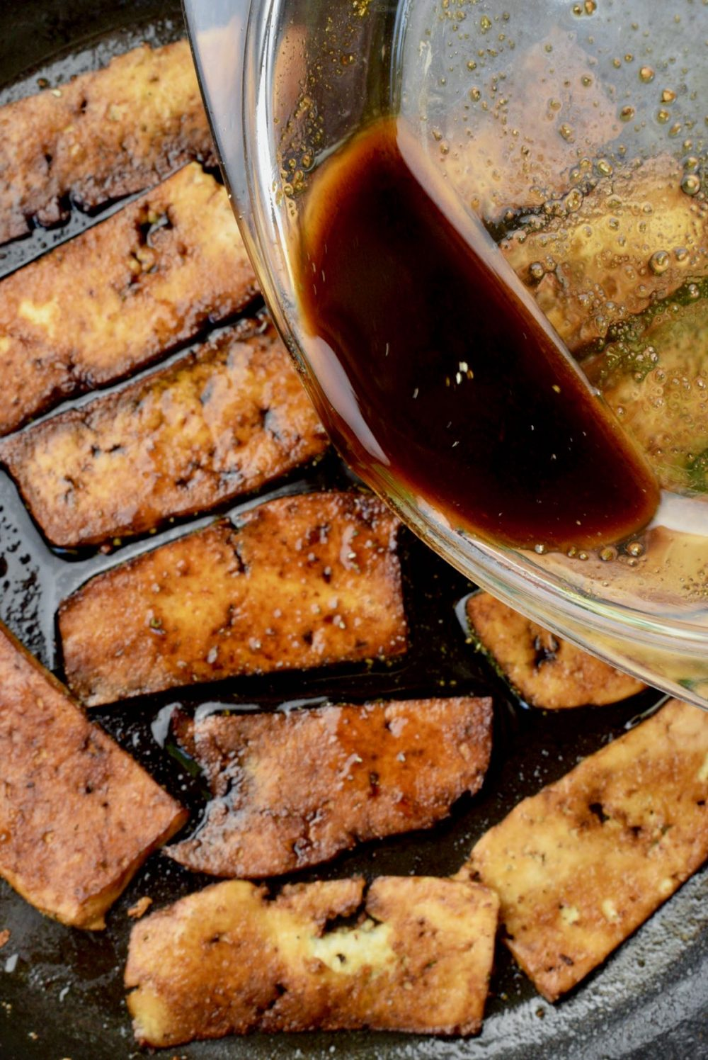 A dark brown marinade is poured over slices of fried tofu in the frying pan.
