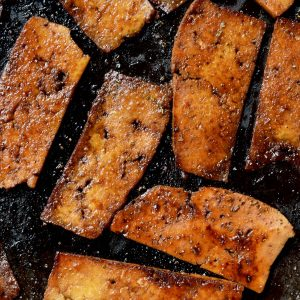 A top-down close-up of several deep brown fried slices of marinated tofu in a frying pan.