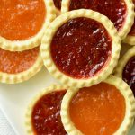 An assortment of jam tarts filled with red berry and apricot jam